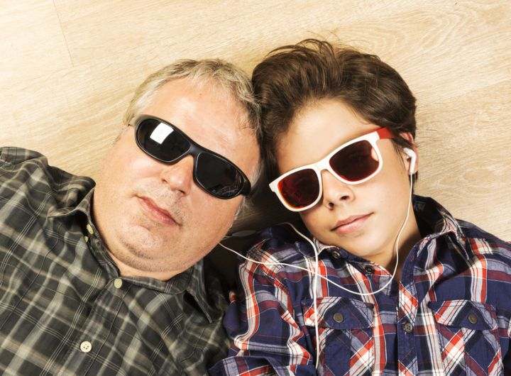 dad and son lying on floor wearing sunglasses, headphones