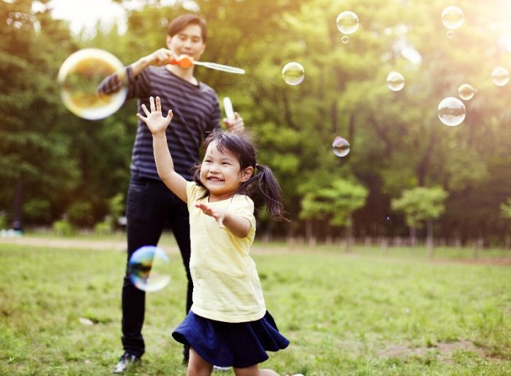 happy little girl blowing bubbles with parent in background