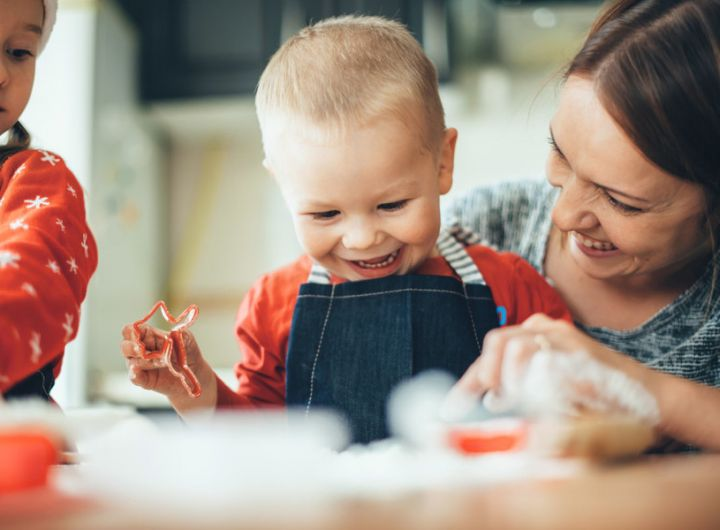 happy baby cuts pastry dough as mother and sibling look on